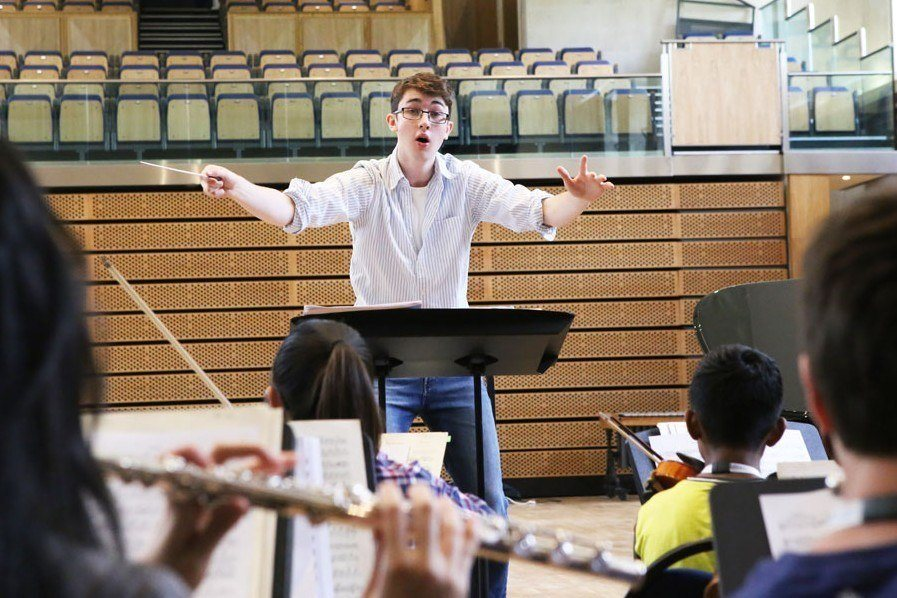 Conducting student with orchestra