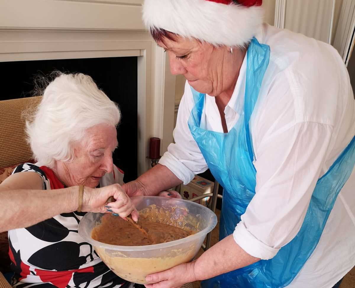 Bernice assists the residents in mixing the cake