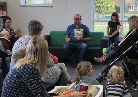 Simon reads the story to children and parents